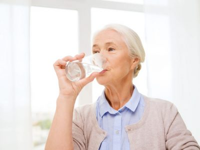 happy senior woman with glass of water at home